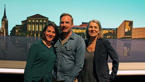 Die Komparsen Pauline Meignan, Martin Schlemmer und Ethel Dadam stehen vor der Kulisse im Fernsehstudio.