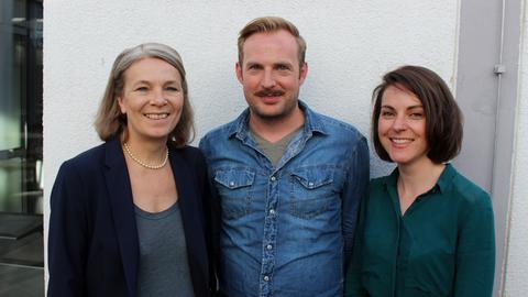 Die Komparsen Ethel Dadam, Martin Schlemmer und Pauline Meignan lächeln in die Kamera.