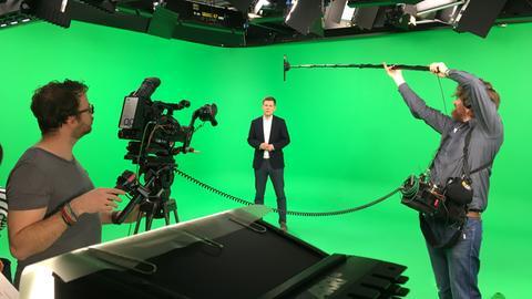 Sebastian Kisters vor grünem Hintergrund im Studio bei den #kurzerklärt-Aufnahmen