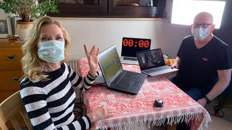 Moderatorin Franziska Reichenbacher und Produktionstechniker Uwe Tapken sitzen mit Mund-Nasen-Masken auf beiden Seiten eines kleinen Tisches mit drei geöffneten Laptops (zu sehen sind die Lotto-Grafik, das Kamerabild und ein Timecode) im Licht eines Scheinwerfers von hinten rechts.