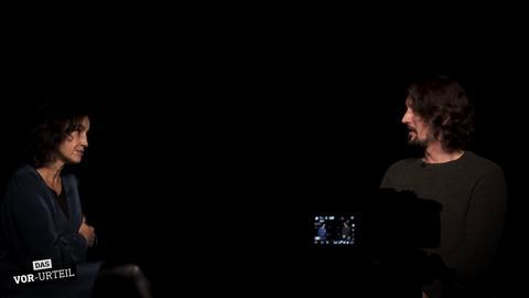 Heike Borufka und Danijel Majic sitzen in einem schwarz ausgekleideten Studio und unterhalten sich.