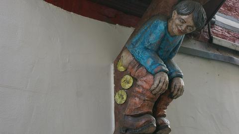 Hölzerne Figur am Fachwerkhaus in Herborn: Muenzschisser