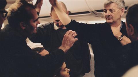 Szene im Flugzeug vor den Gepäckklappen: Journalisten-Gedränge um Außenminister Joschka Fischer 2002.