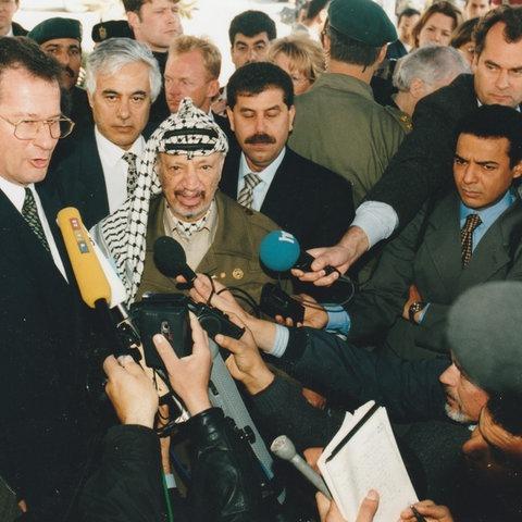 Der frühere Außenminister Klaus kinkel und Palästinenserführer Jassir Arafat umringt von einem Pulk Journalist*innen mit mikrofonen, darunter auch Christopher Plasss mit hr-Mikrofon, Aufnahme von 1997