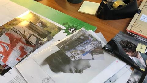 Schreibtisch mit Tatortfotos.