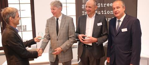Laudator Reto Schlatter (Schweizer Journalistenschule) gratuliert Stefan Jäger, Ingo Nathusius und Andreas Niklaus (State Street Corporation).
