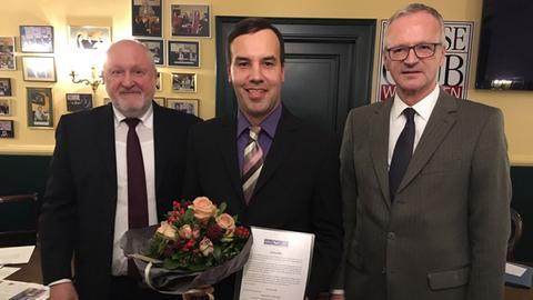 Rick Gajek hält Blumenstrauß, daneben Werner D'Inka und Peter Wagner