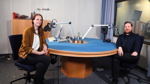 Alisa Schmitz und Marvin Mendel sitzen in einem Tonstudio und schauen in die Kamera.