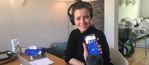 YOU FM-Moderatorin Susanka sitzt an einem Tisch vor einem Laptop und hält ein Handy in die Kamera