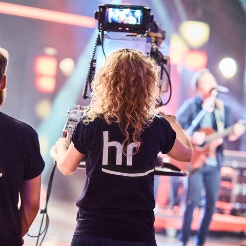Kameraleute filmen eine Band auf einer Bühne