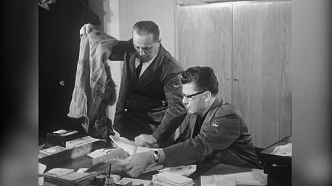 Schwarzweißaufnahme: Ein Mann mit einem Leinensack kippt daraus Briefbündel auf den Schreibtisch einen Postbeamten, der diese sogleich untersucht.