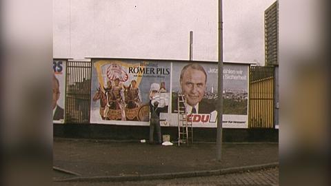 Mann überklebt Plakate auf einer Plakatwand