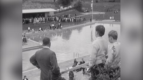 Drei Personen im Schwimmbad schauen auf das Schwimmbecken.