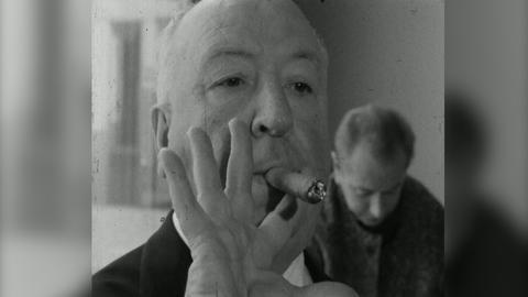 Alfred Hitchcock raucht eine Zigarre.