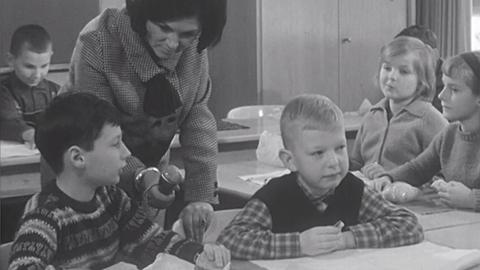 1963: Reporterin mit Schülern im Klassenzimmern