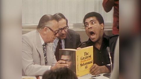Muhammad Ali umringt von Reportern hält ein Buch in der Hand und zieht eine Grimasse