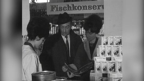 Schwarz-Weiß-Bild: Ein Paar lässt sich an einer Fischtheke von einer Verkäuferin mit einer Broschüre über Reisen informieren.