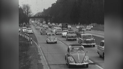 Schwarz-Weiß-Bild von VW-Käfern, die dicht gedrängt auf der Autobahn fahren