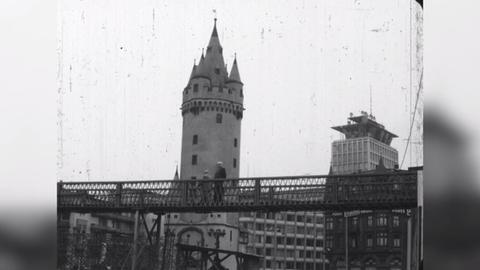 Schwarz-Weiß-Aufnahme des Eschenheimer Turms. Im unteren Drittel ist eine stählerne Fußgängerbrücke vor dem Turm zu sehen, auf der Menschen laufen.