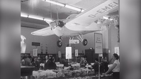 """In einem Frankfurter Kaufhaus hängt über Wühltischen mit Wäsche ein Flugzeug (""""Tipsy Nipper"""") unter der Decke"""