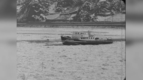"""Einstellung aus einem """"hessenschau""""-Beitrag von 1963. In Schwarz-Weiß ist der zugefrorene Rhein mit einem kleinen Schiff darauf zu sehen."""