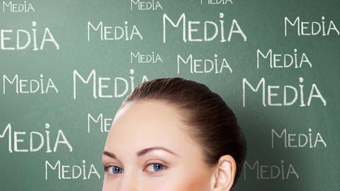"""Ausschnitt Frauengesicht vor tafelähnlichem Hintergrund mit den Schriftzügen """"Media"""""""