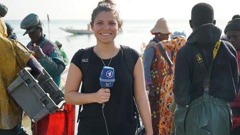 Dunja Sadaqi mit hr-Mikrofon am Ufer, im Hintergrund Menschen