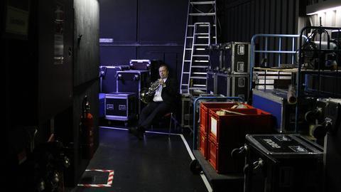 Ein Bläser des hr-Sinfonieorchesters sitzt im Frack hinter der Bühne zwischen vielen Transportkisten mit Musikinstrumenten