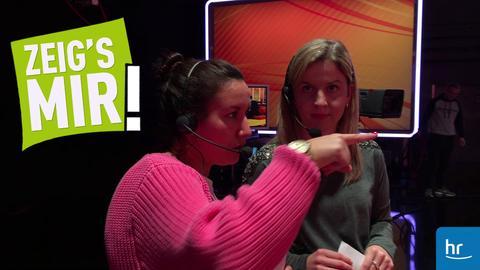 """Aufnahmeleiterin Iris erklärt Caro die Aufteilung im Fernsehstudio von """"Dings vom Dach""""."""