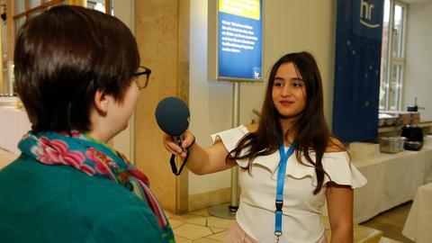 Ein Mädchen hält einer Frau ein Mikrofon hin