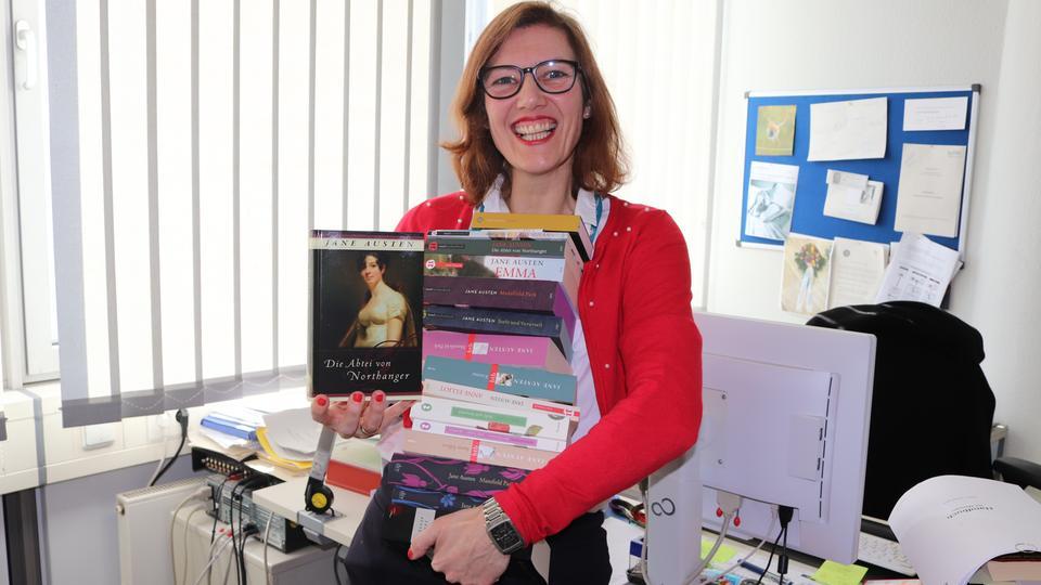 Cordula Huth mit einem Stapel Jane-Austen-Büchern in der Hand.