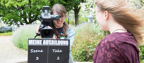 Zwei Schülerinnen mit einer Filmklappe