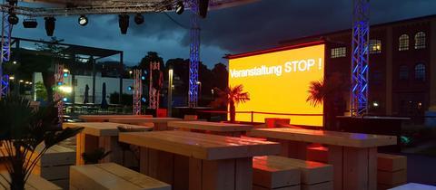 """Dunkle Wolken hängen über dem menschenleeren hr-Beach im """"hr-Treff"""". Auf einem Bildschirm im Vordergrund steht """"Verasntaltung STOP!""""."""