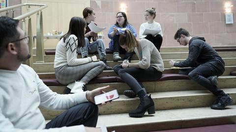 Einige Jugendliche sitzen gemeinsam auf Stufen, tauschen sich aus und schreiben Dinge auf.