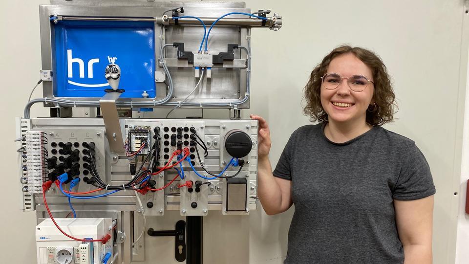 Ingrid Schmidt neben einer Apparatur aus Metall, darauf das hr-Logo