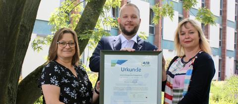 Die AfB gemeinnützige GmbH übergab eine Urkunde für das gemeinsame sozial-ökologische Wirken.  Von links: Brigitte Puchert (Materialwirtschaft), Alexander Schwander (Partner-Manager AfB) und Maike Sawinski (Leiterin Liegenschaftsverwaltung)
