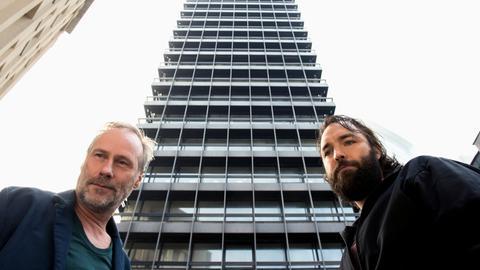 "Szene aus dem hr-Tatort ""Der Turm"": Kommissar Paul Brix (Wolfram Koch, links) und Assistent Jonas (Isaak Dentler) vor einem riesigen Büroturm"