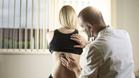 Ein Arzt untersucht eine Patientin und hört ihr den Rücken ab.