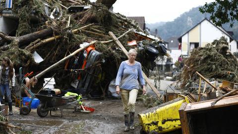Frau steht vor einem vom Wasser zerstörten Auto, auf dem entwurzelte Bäume liegen.