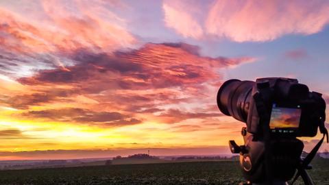 Bunter Himmel, im Vordergrund eine Spiegelreflexkamera.