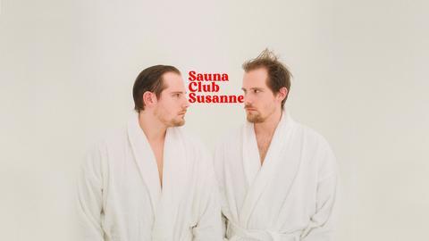 Key Visual von Saunaclub Susanne: Die beiden Hosts stehen sich im Bademantel gegenüber