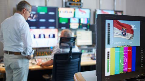 Innenaufnahme Studio Wiesbaden. Blick auf Monitore und zwei Mitarbeiter von hinten.