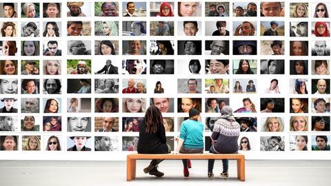 Im Museum o.ä.: Vor einer riesigen Wand mit Porträtfotos verschiedenster Menschen sitzen drei Fraue auf einer Bank und betrachten die Gesichter