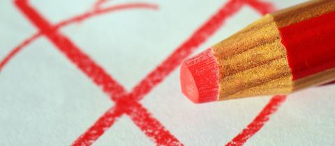 Roter Stift und gemaltes Kreuzchen auf einem Zettel