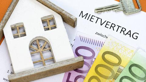 Ein Holzhaus liegt auf einem Mietvertrag und Geldscheinen