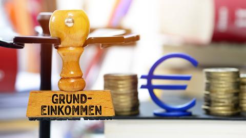 """Ein Stempel mit dem Aufdruck """"Grundeinkommen"""" vor einem Eurozeichen"""